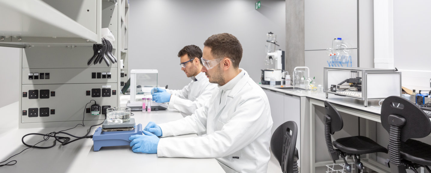 Two researchers sat at a lab bench handling equipment