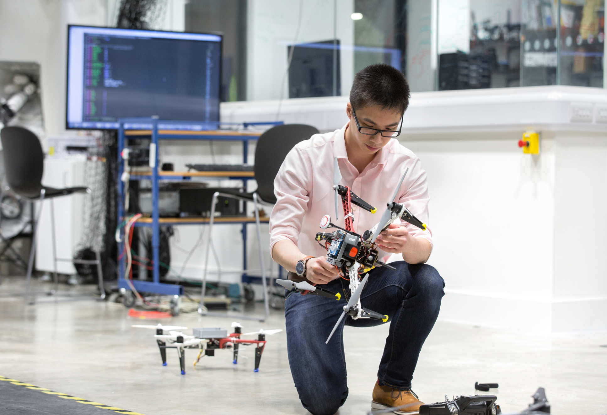 Man crouching and holding a drone, with another behind him