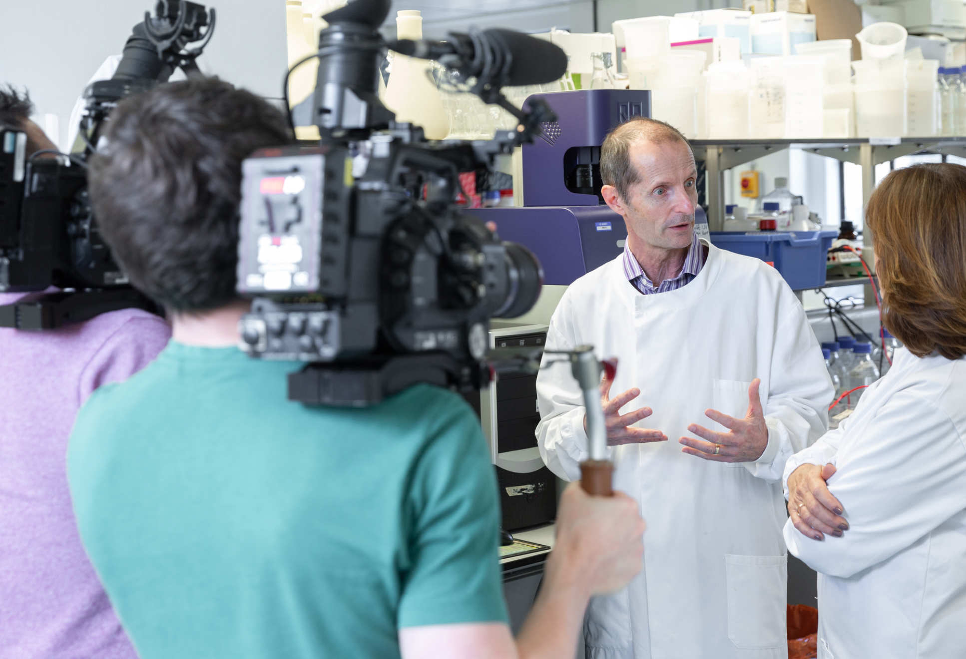 Professor Robin Shattock with a camera crew in the lab