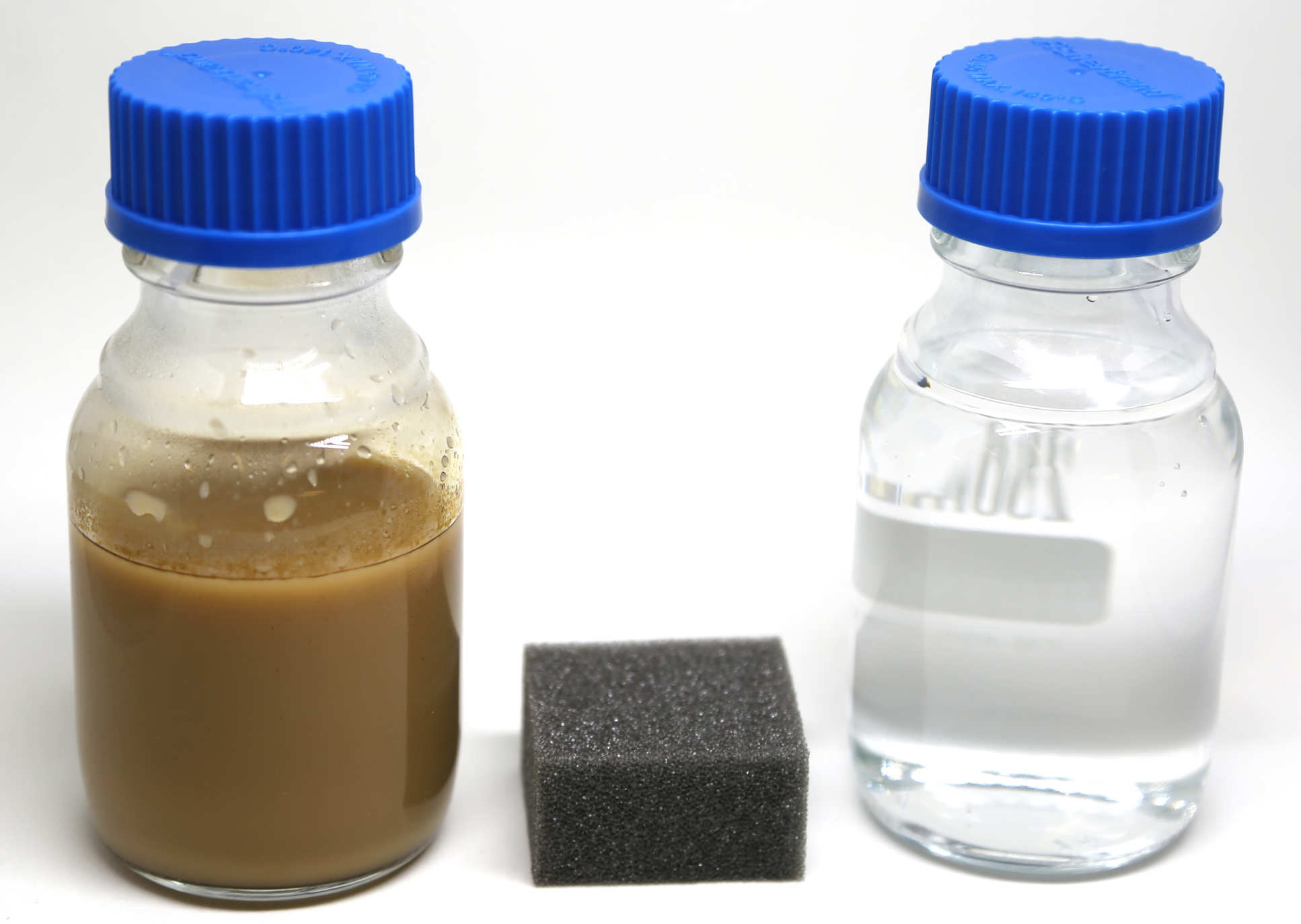 Photo of two bottles - one containing brown liquid, the other containing clear liquid. Between the bottles is a small black sponge.