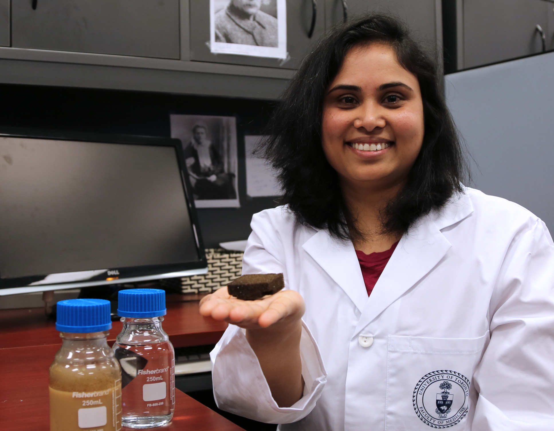Photo of Dr Cherukupally with the sponge and 'before and after' water samples (one bottle containing brown liquid; the other, clear, clean liquid after sponge treatment) in her lab at the University of Toronto