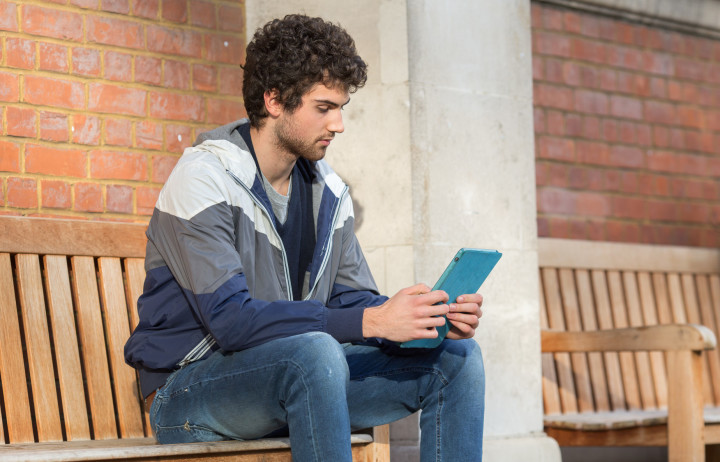 A student in a grey coat sitting on a bench and looking at an iPad
