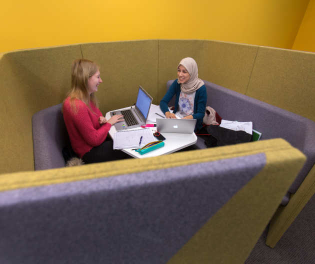 Students chatting together in the library