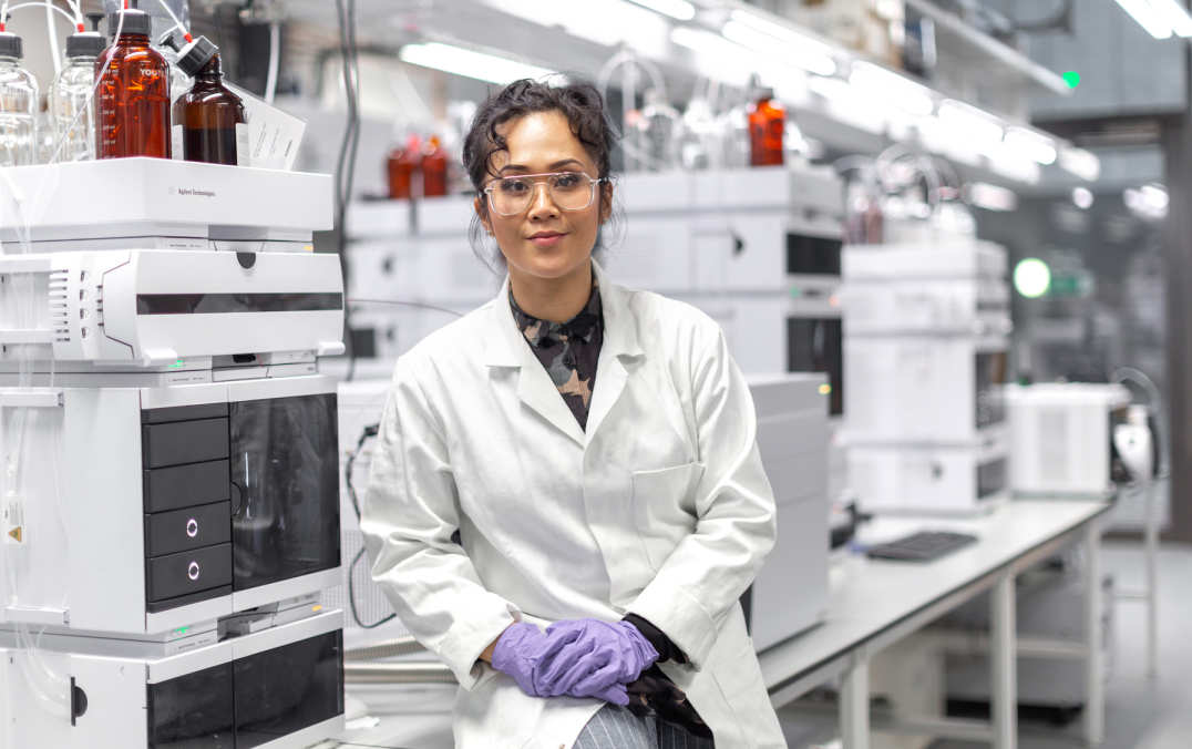 Woman in lab with lab coat, gloves and goggles smiling to camera