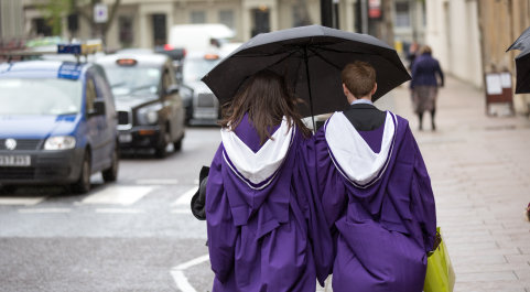 Two graduates wearing their graduation gowns