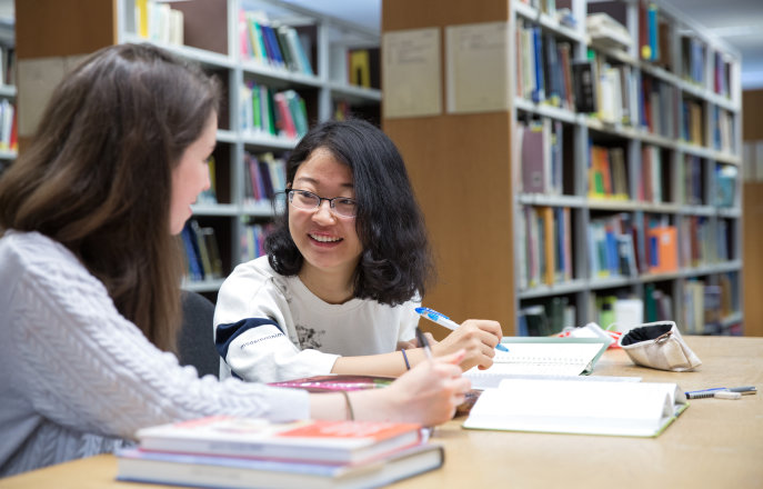 Two students working together in the library