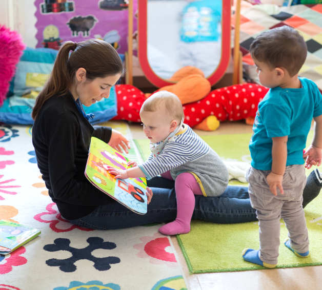 Baby on nursery mat with adult