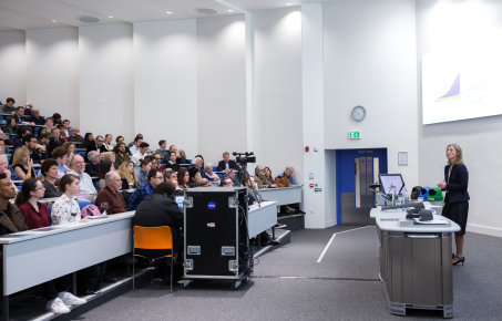 Woman giving a talk in a lecture theatre