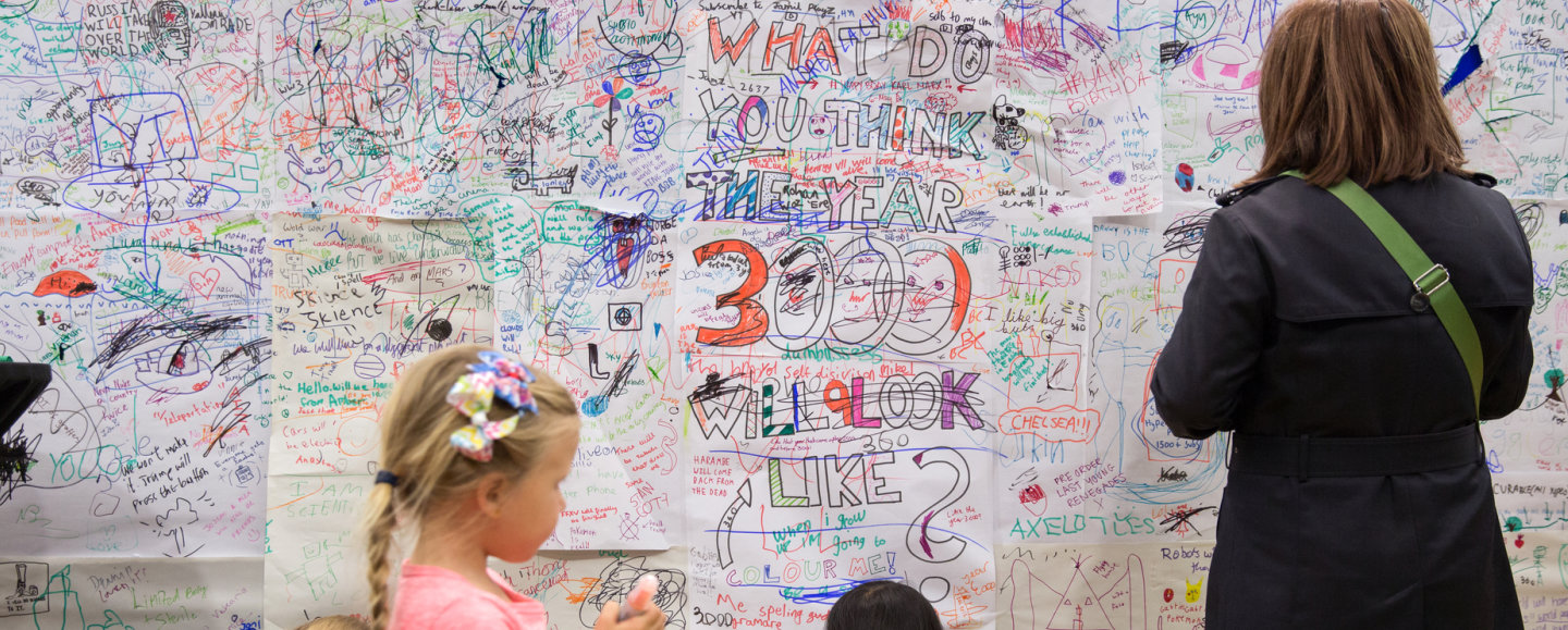 Members of the public contribute to an ideas wall at the Imperial festival