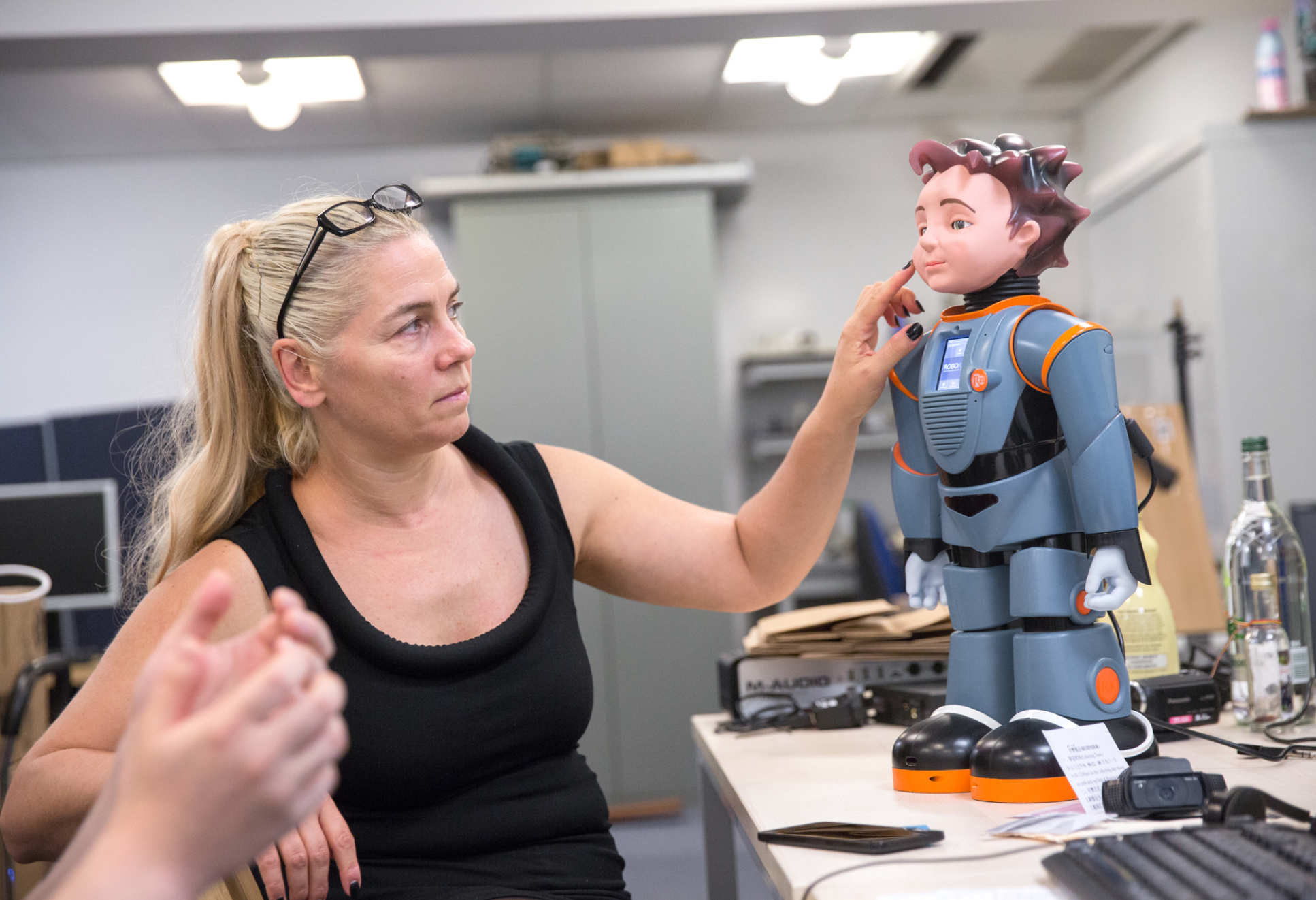 Professor Maja Pantic points at her robot