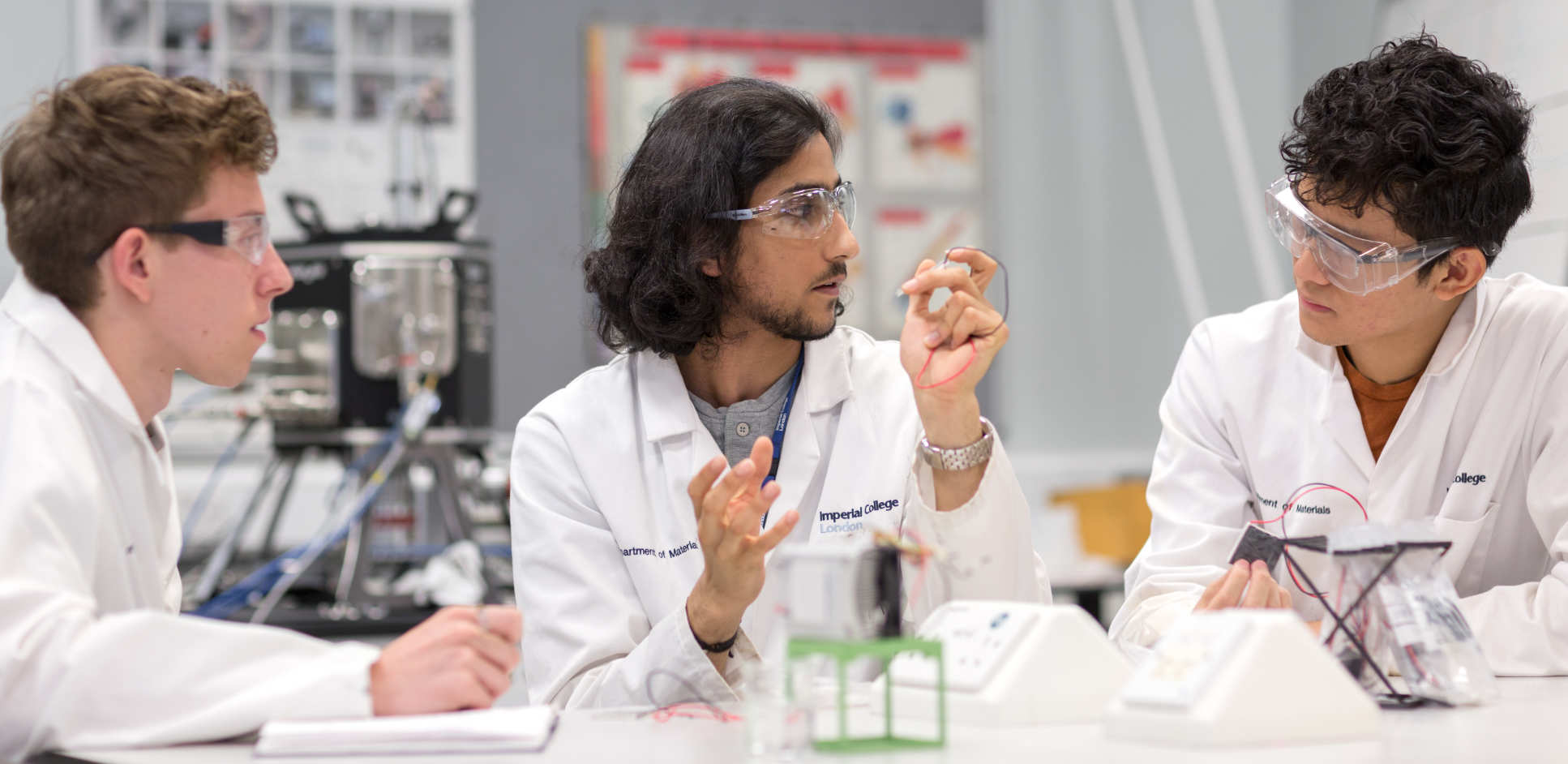 three students discussing a project in a lab
