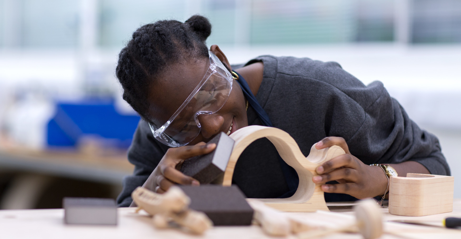 A young black woman sanding a wooden object.