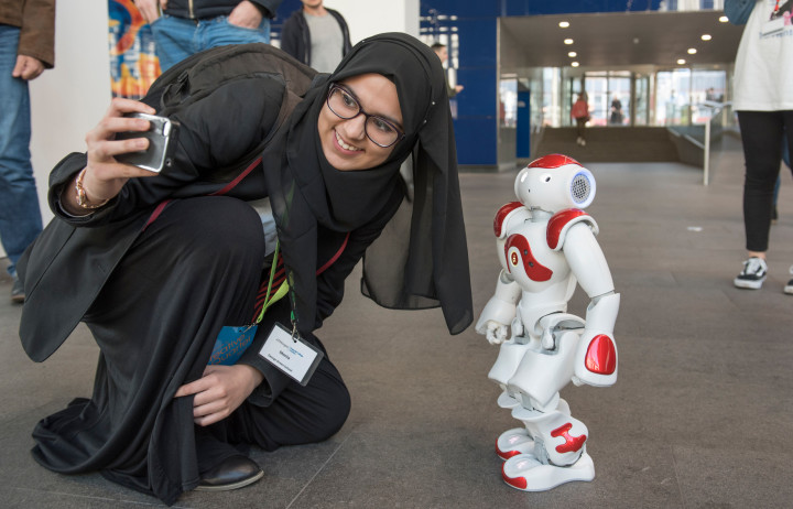A young woman stoops down to take a photo with a humanoid robot.