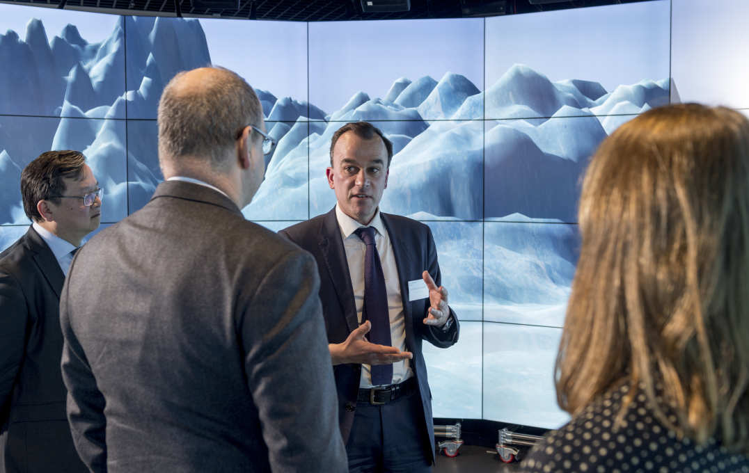 Martin Siegert speaks to the prince in front of a large screen showing Antarctic landscape