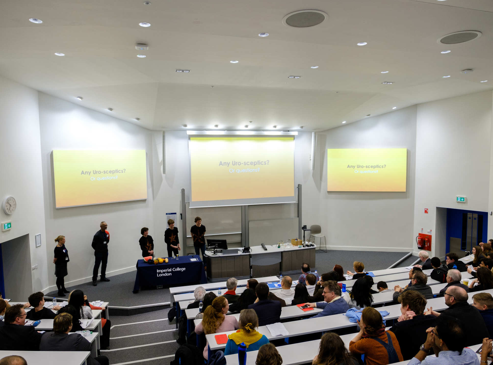 School students presenting their ideas to the audience and panel of judges in a lecture theatre