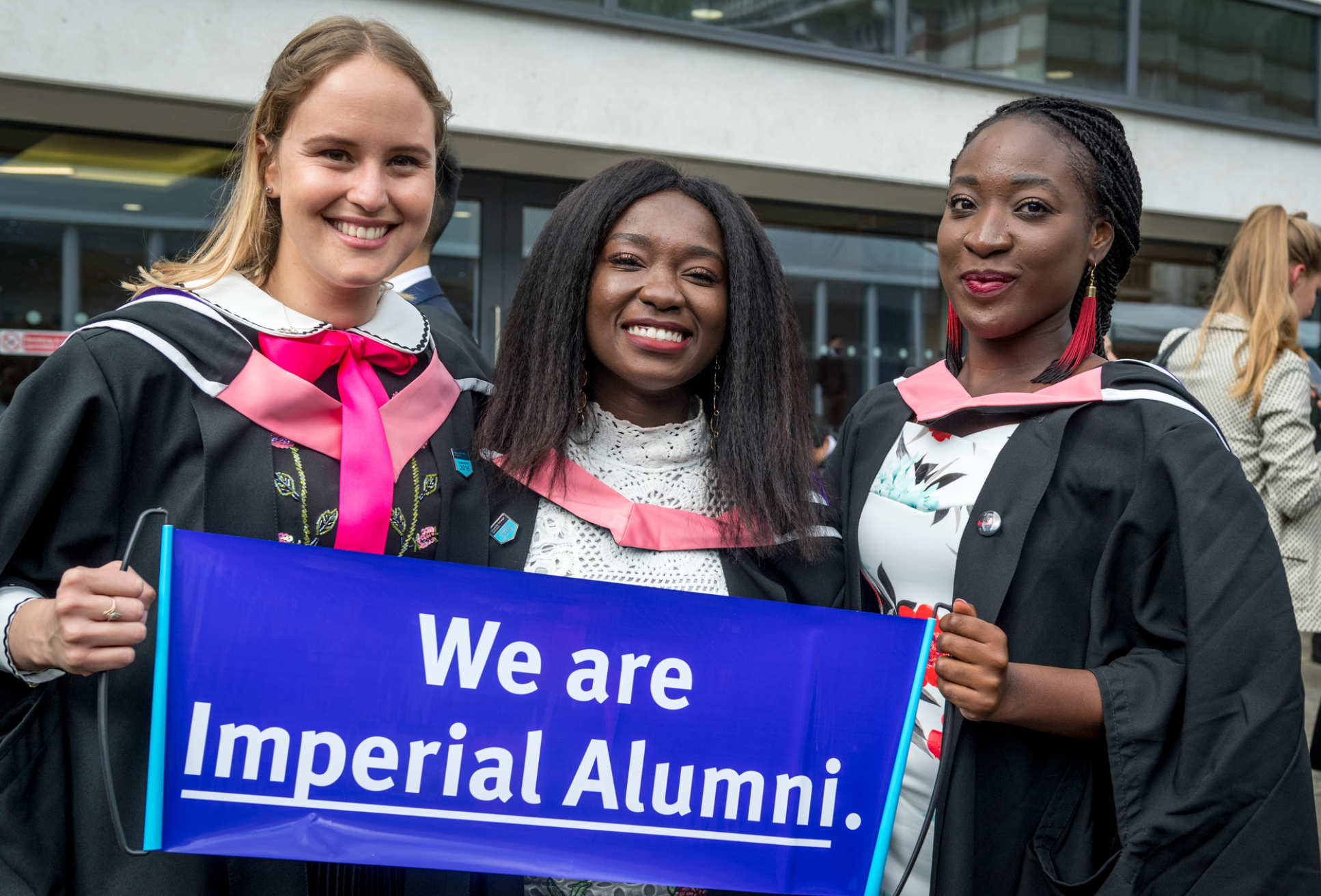 Students hold up 'We are Imperial Alumni' sign