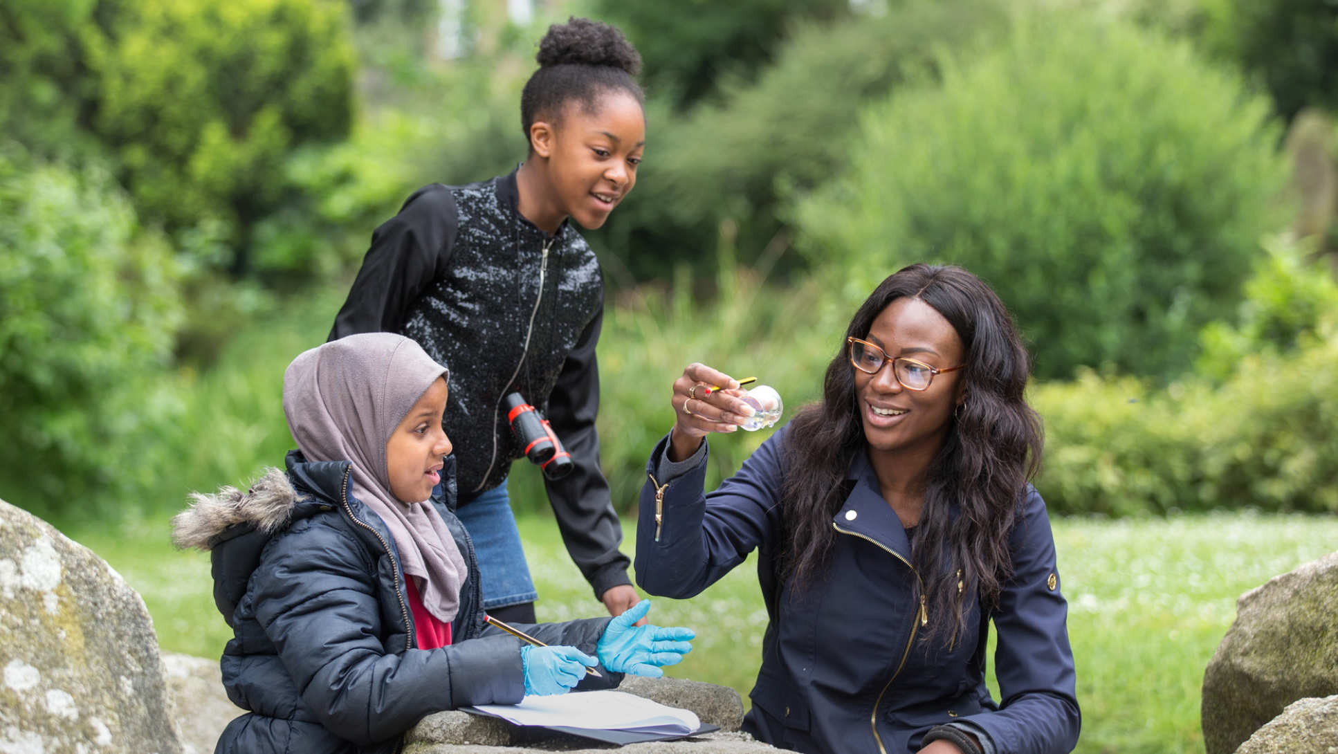 Two children and a woman recording details of the insects they have found in a park.