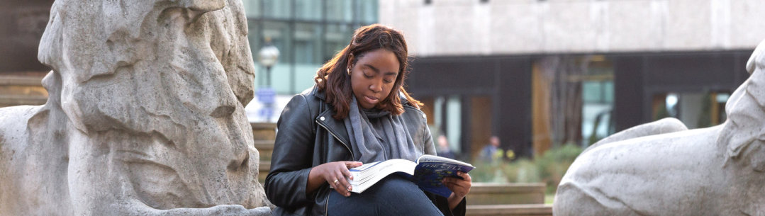 A student sits by the stone lion at the base of the Queen's Tower, reading a text book