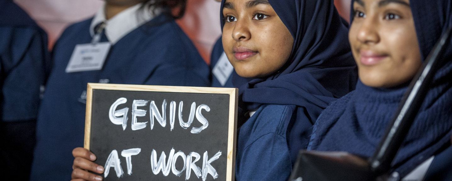 An image of students holding a sign which says 'Genius at work'