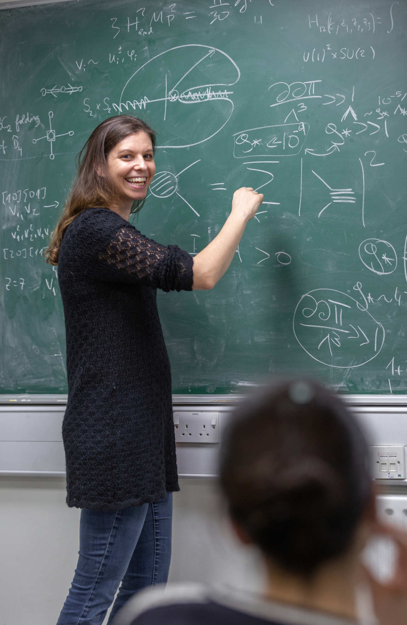 Professor Claudia de Rham teaching at a blackboard