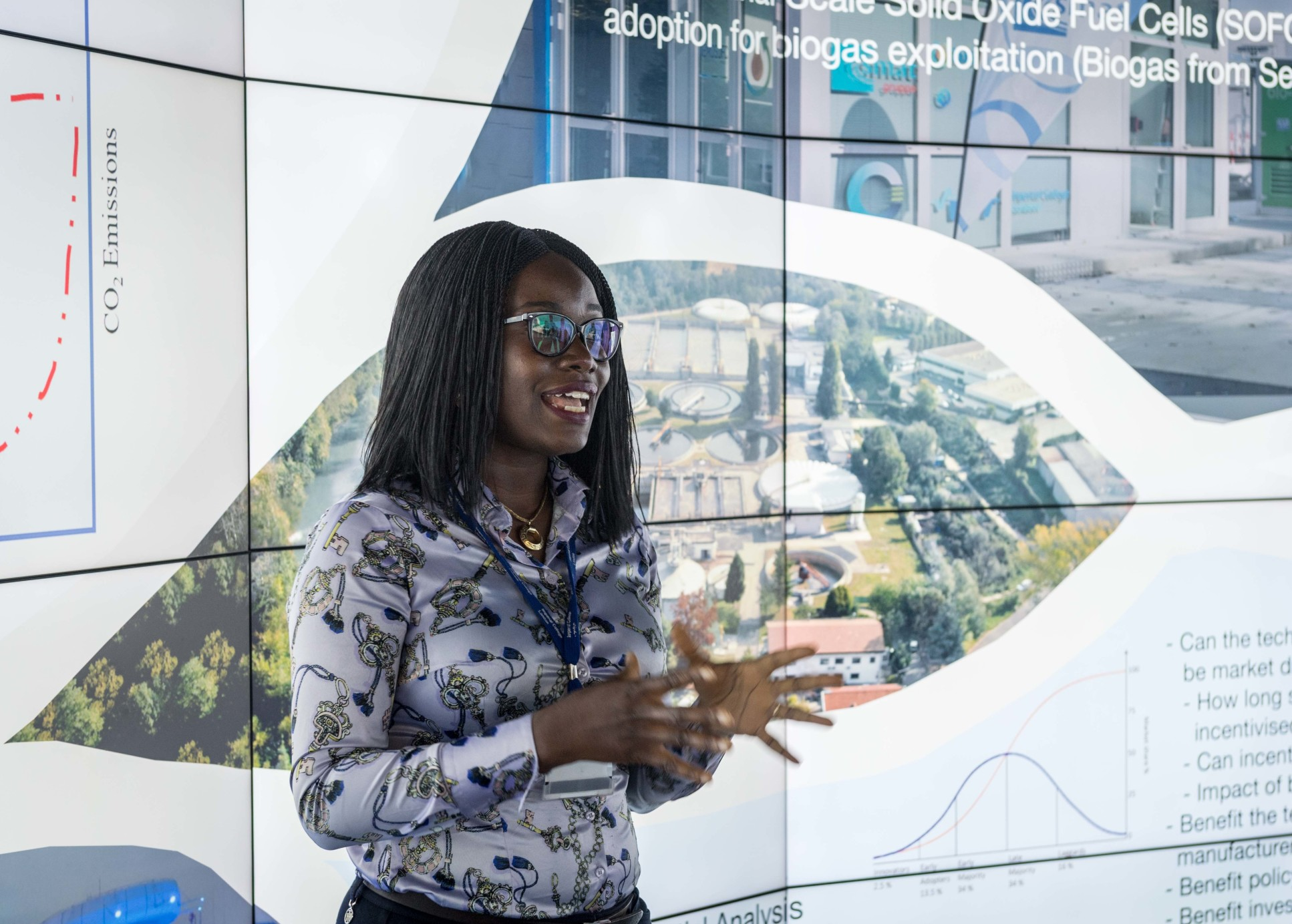 Gbemi Oluleye, a black woman in her mid thirties, addresses an audience, she stands in front of a video screen showing an aerial photo of an industrial plant. Gbemi wears a light blouse and has dark thinly braided hair and glasses.