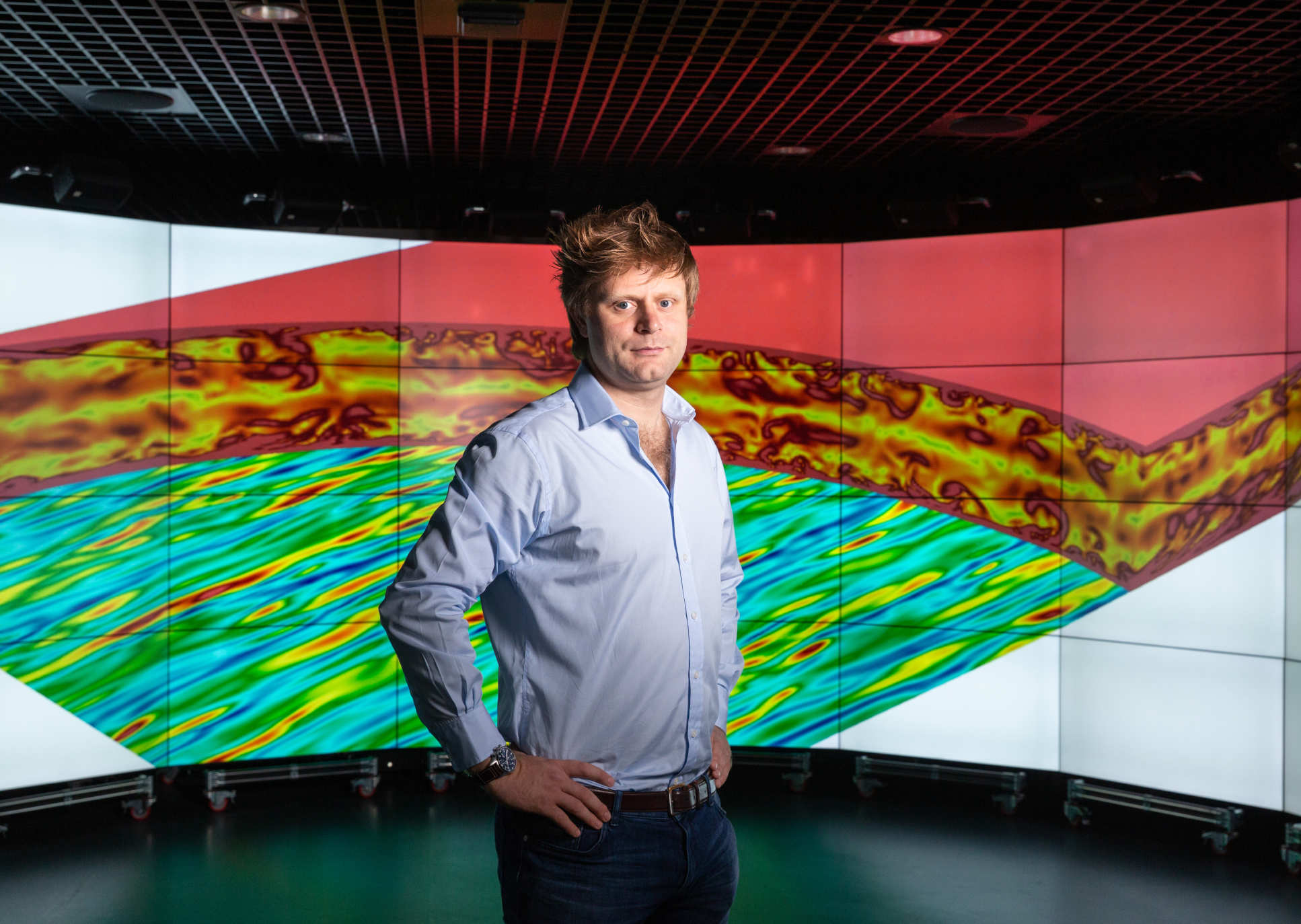 Dr Peter Vincent in front of a screen showing one of the flow simulations