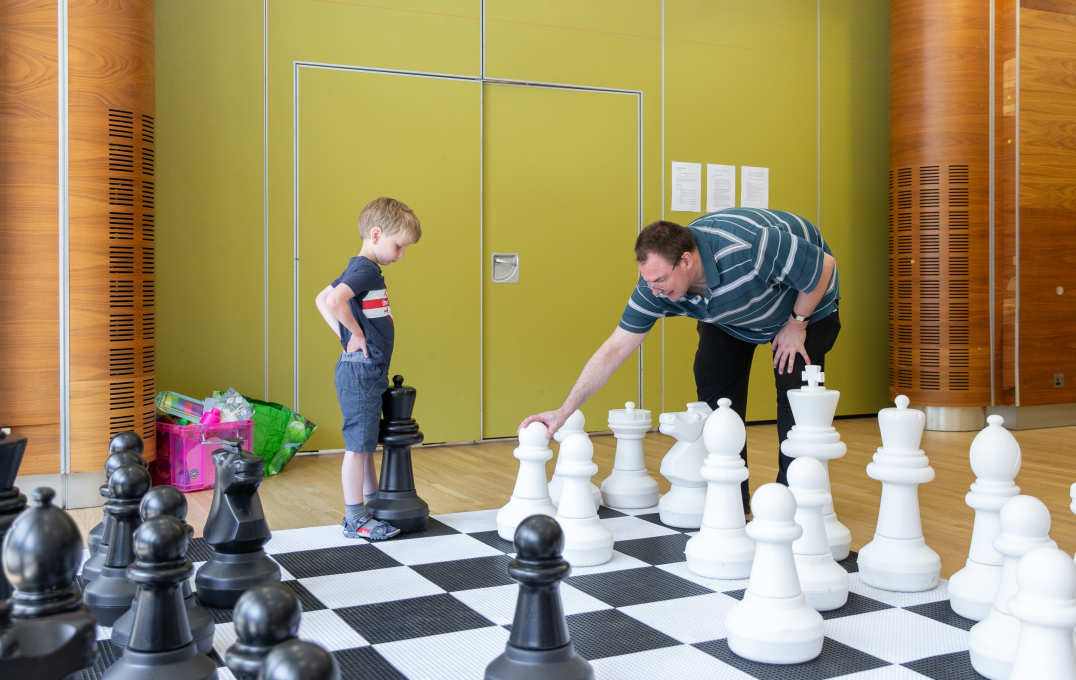 A boy and a man play giant chess together at the annual Bring Your Child To Work Day