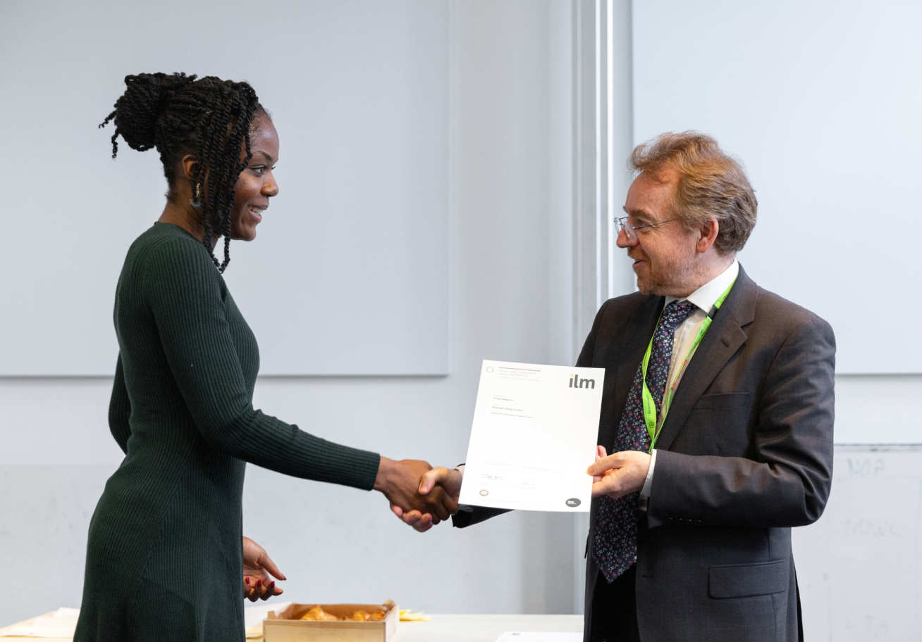 woman collects certificate and shakes man's hand