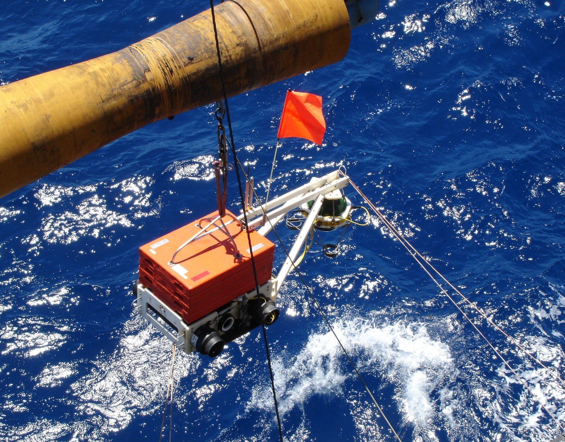 A photo of a seismometer, in a large orange box, being deployed into the sea from a research vessel