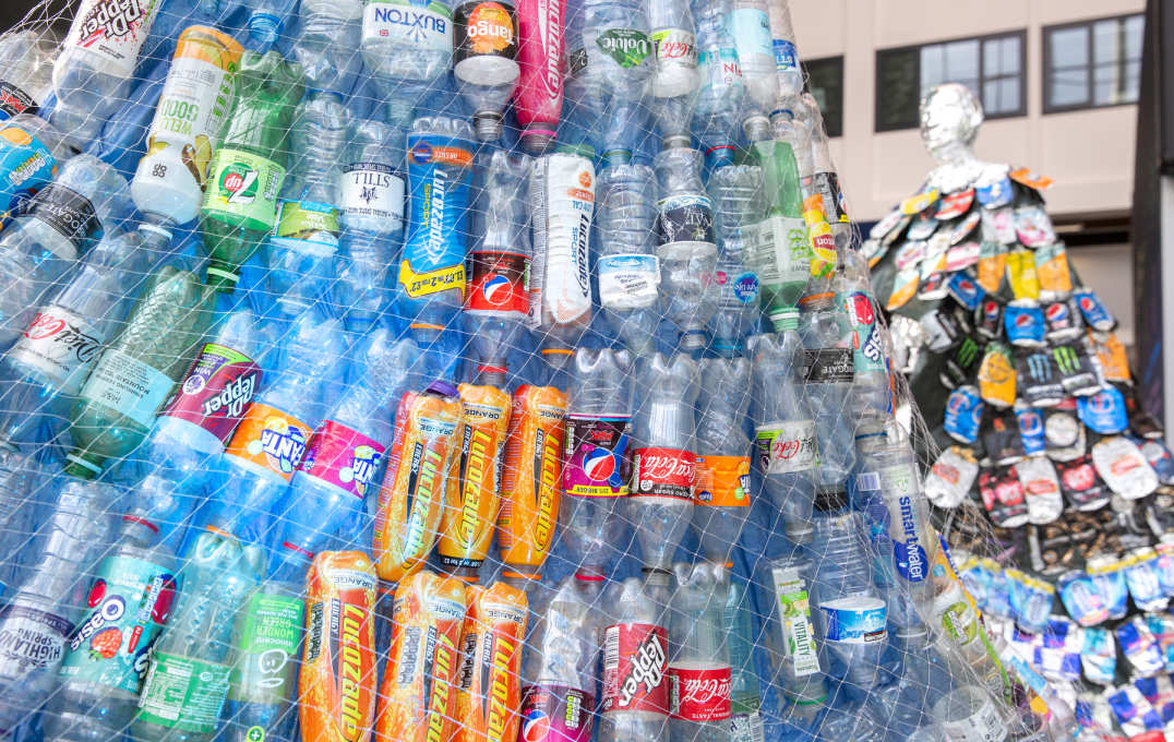 close up of plastic bottles held together by netting. Bottles reado Lucozade, Fanta, Dr Pepper, Diet Coke, Coca cola, Smart water, Buxton