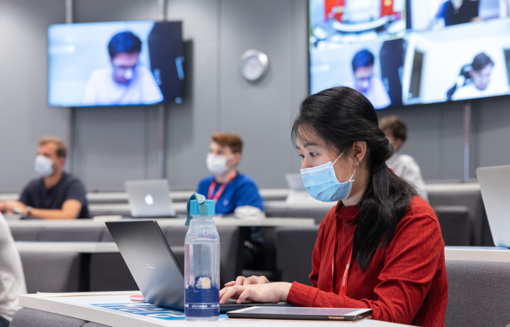 A student wearing a red top and a blue face mask typing on a laptop in a lecture in the Business School