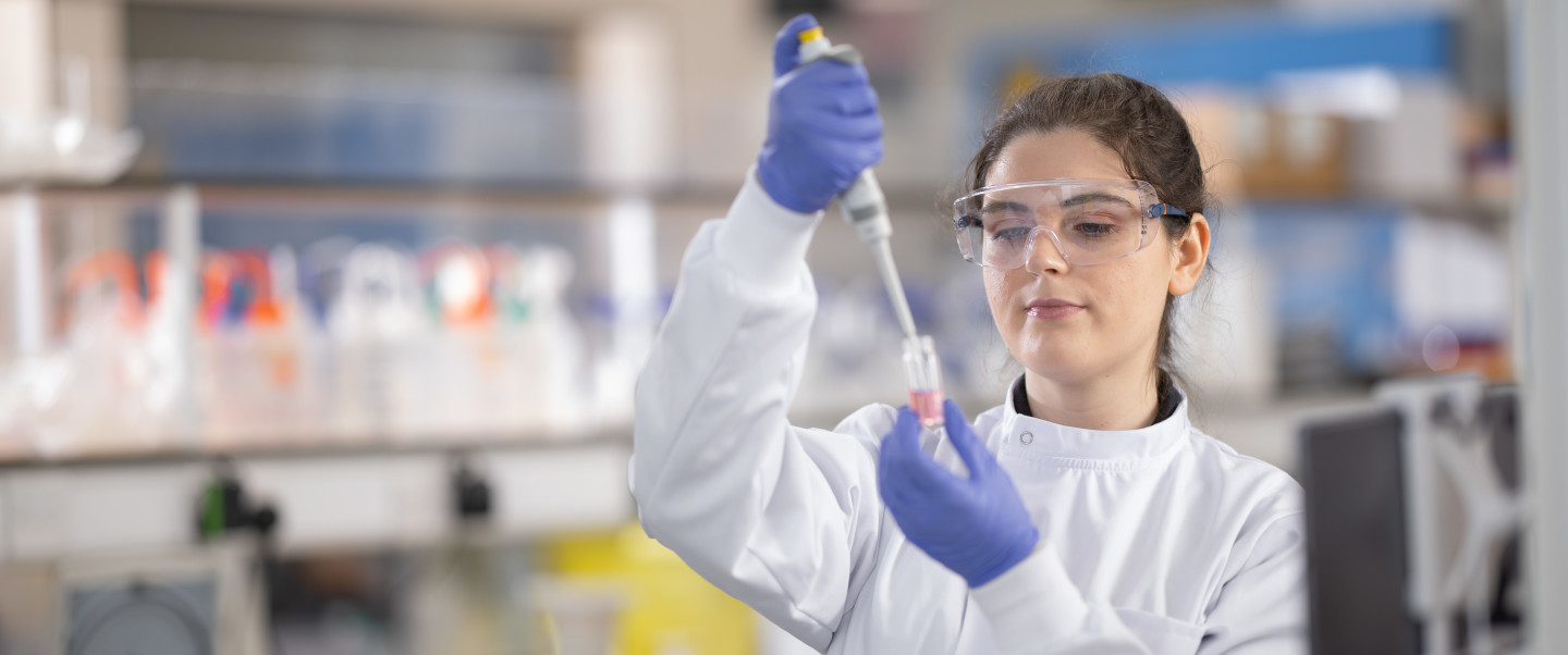 A young woman working in a lab, using a pipette