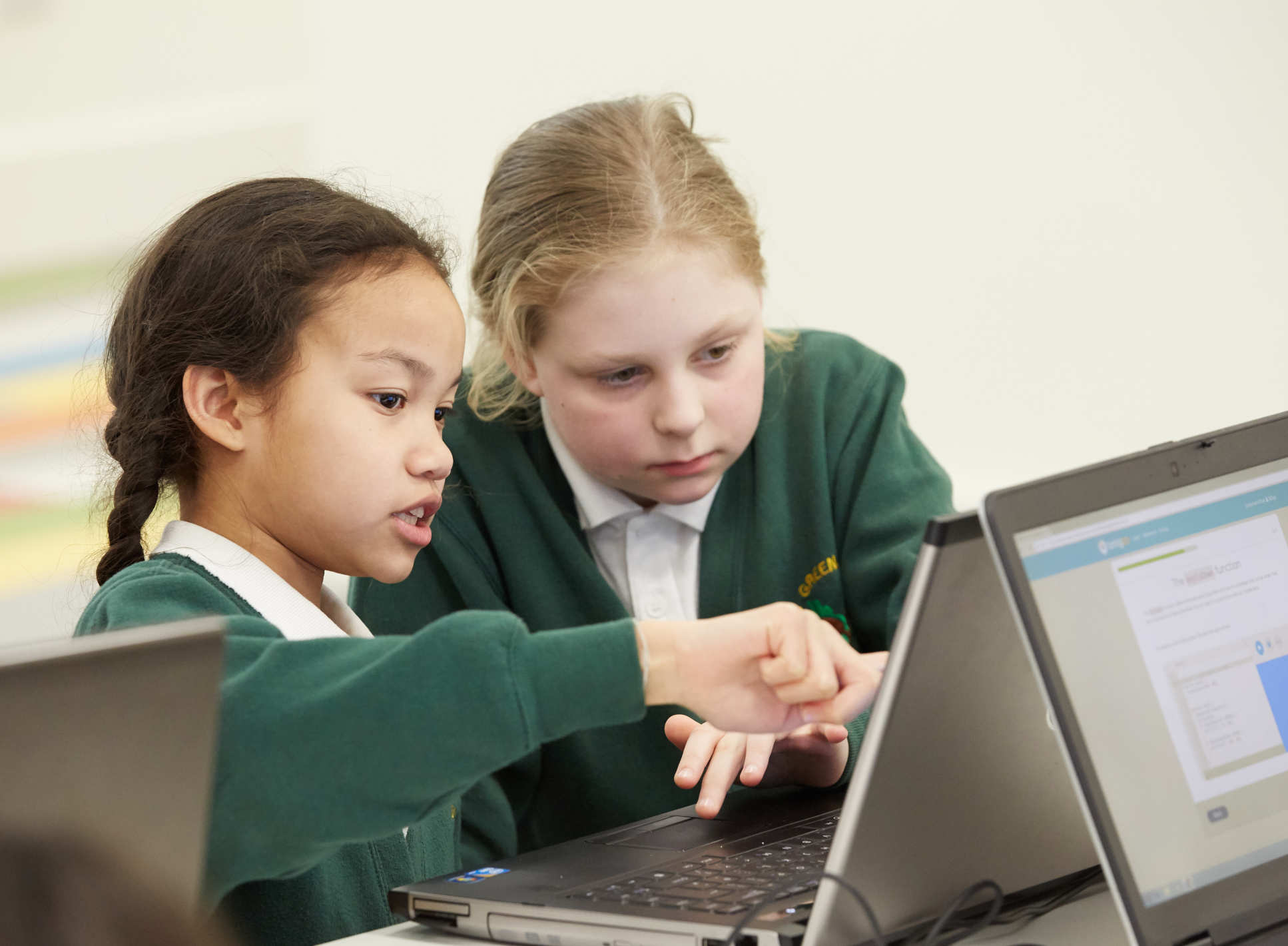 two girls focus on a laptop screen image