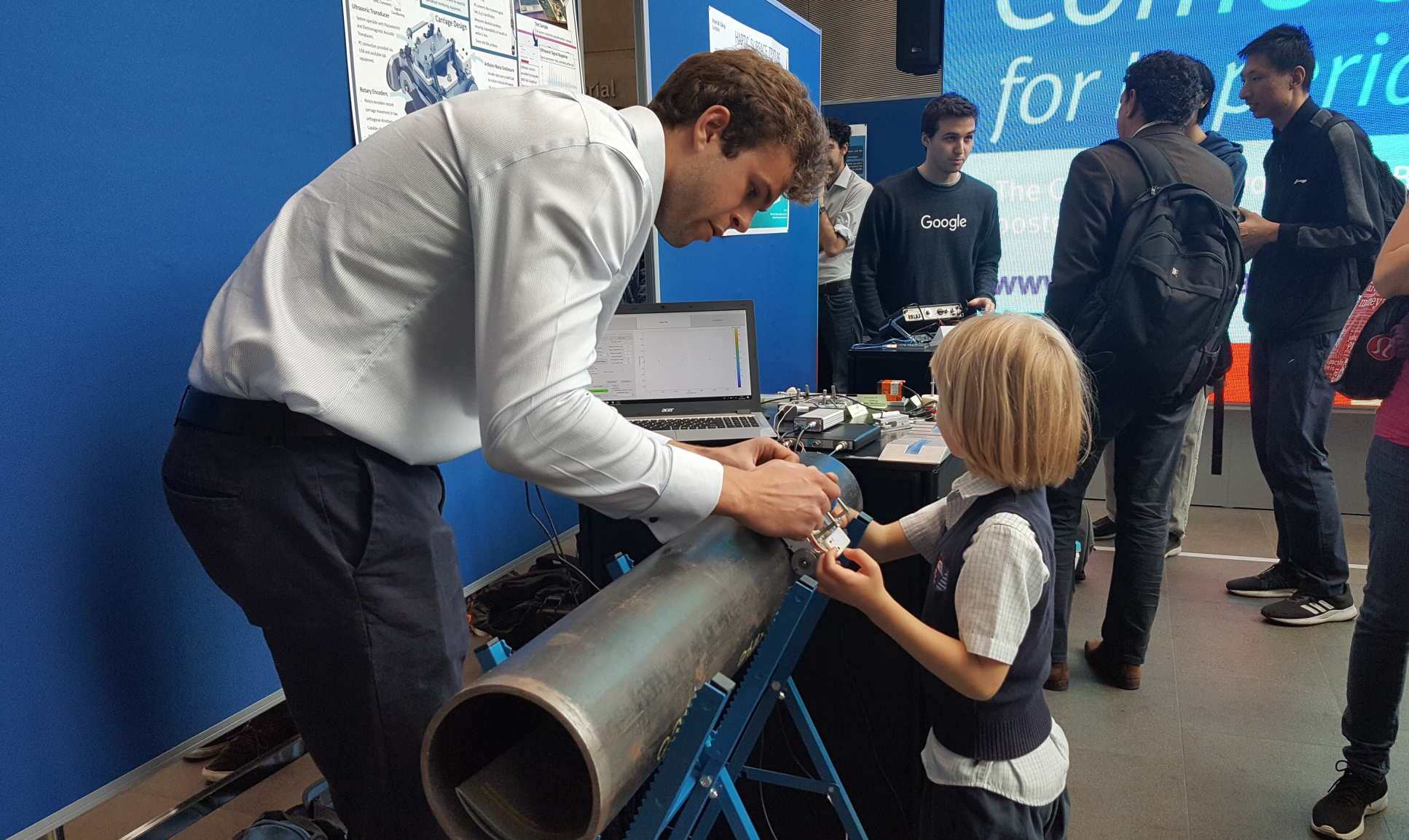 Inspiring the younger generations: student Ben Hambrook explains his project on ultrasonics to a five year old visitor