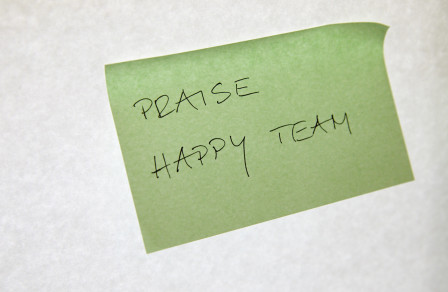 Post-it note saying 'praise happy team'