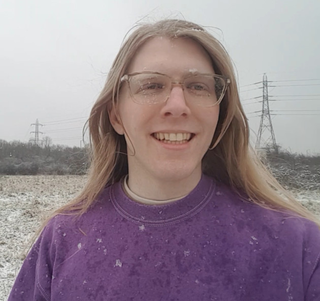 Robin Lamboll, a smiling person with white skin and long blonde hair and glasses stands in a snowy field