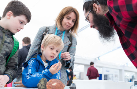 A family at the Festival looking at rocks with a researcher