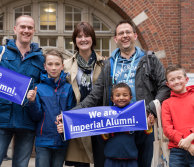A family at Alumni Weekend holding banners
