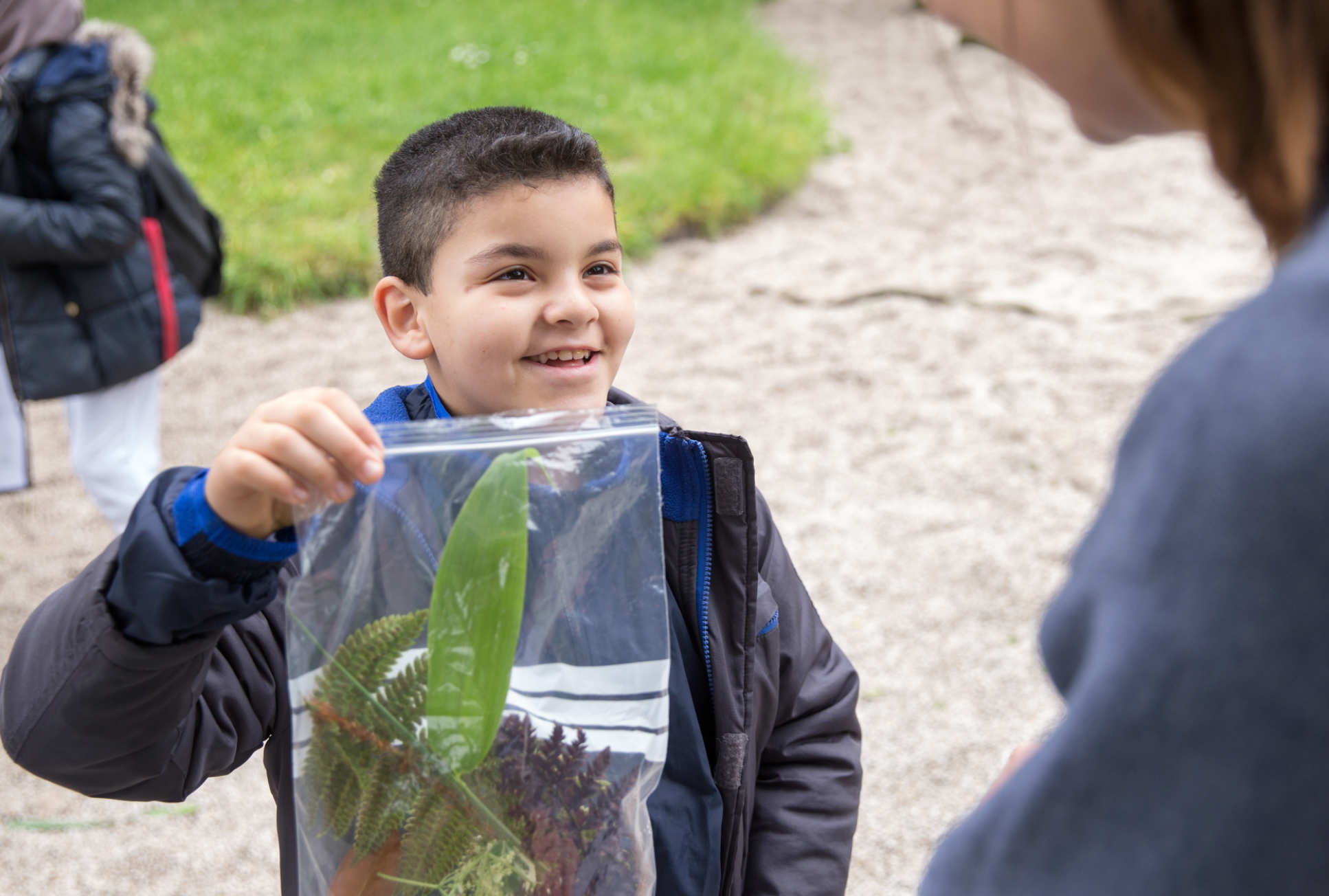 Child holding a bag of leaves