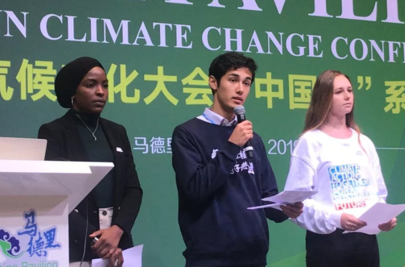 Three students present to an audience from a stage