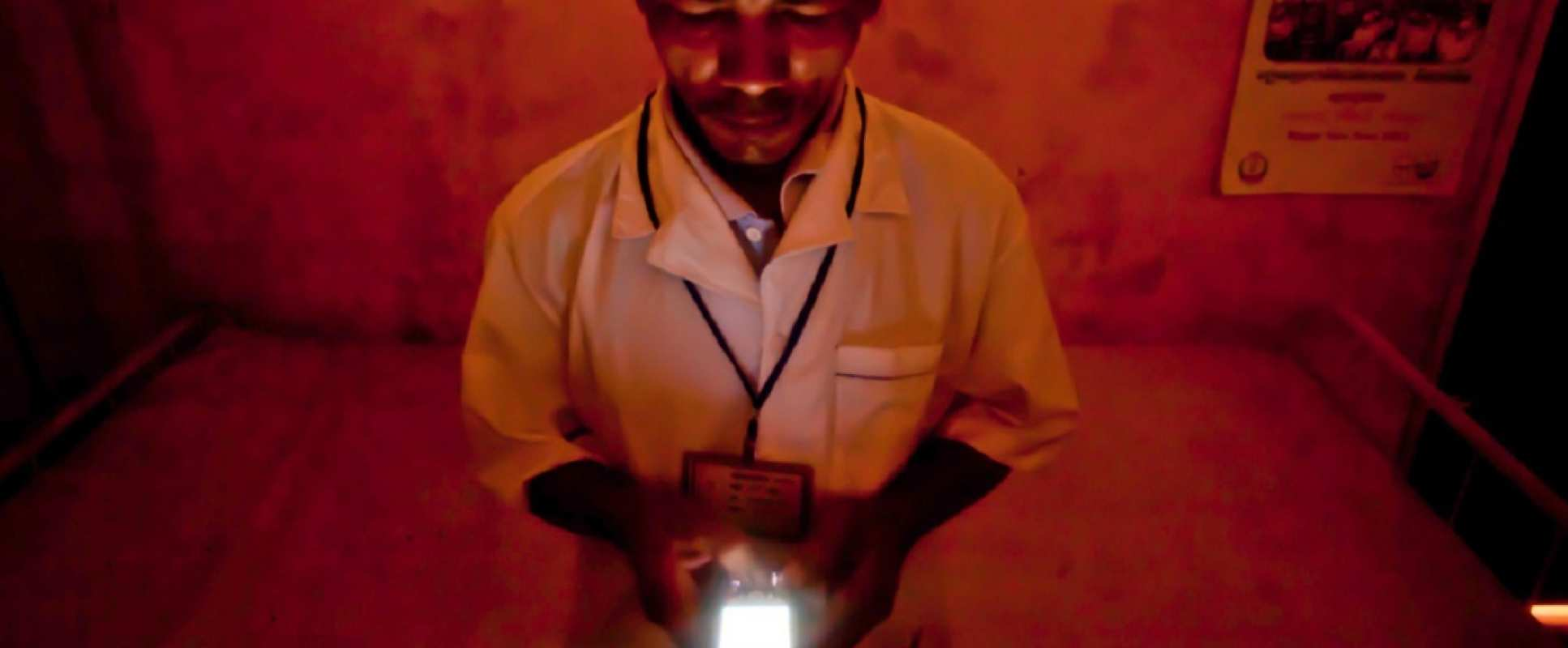 Member of medical staff using a mobile phone to report on malaria