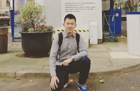 Hang Guo kneeling in front a Imperial College London sign