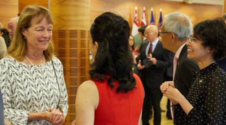 Alice Gast speaks to two visitors at a celebration of Singapore National Day