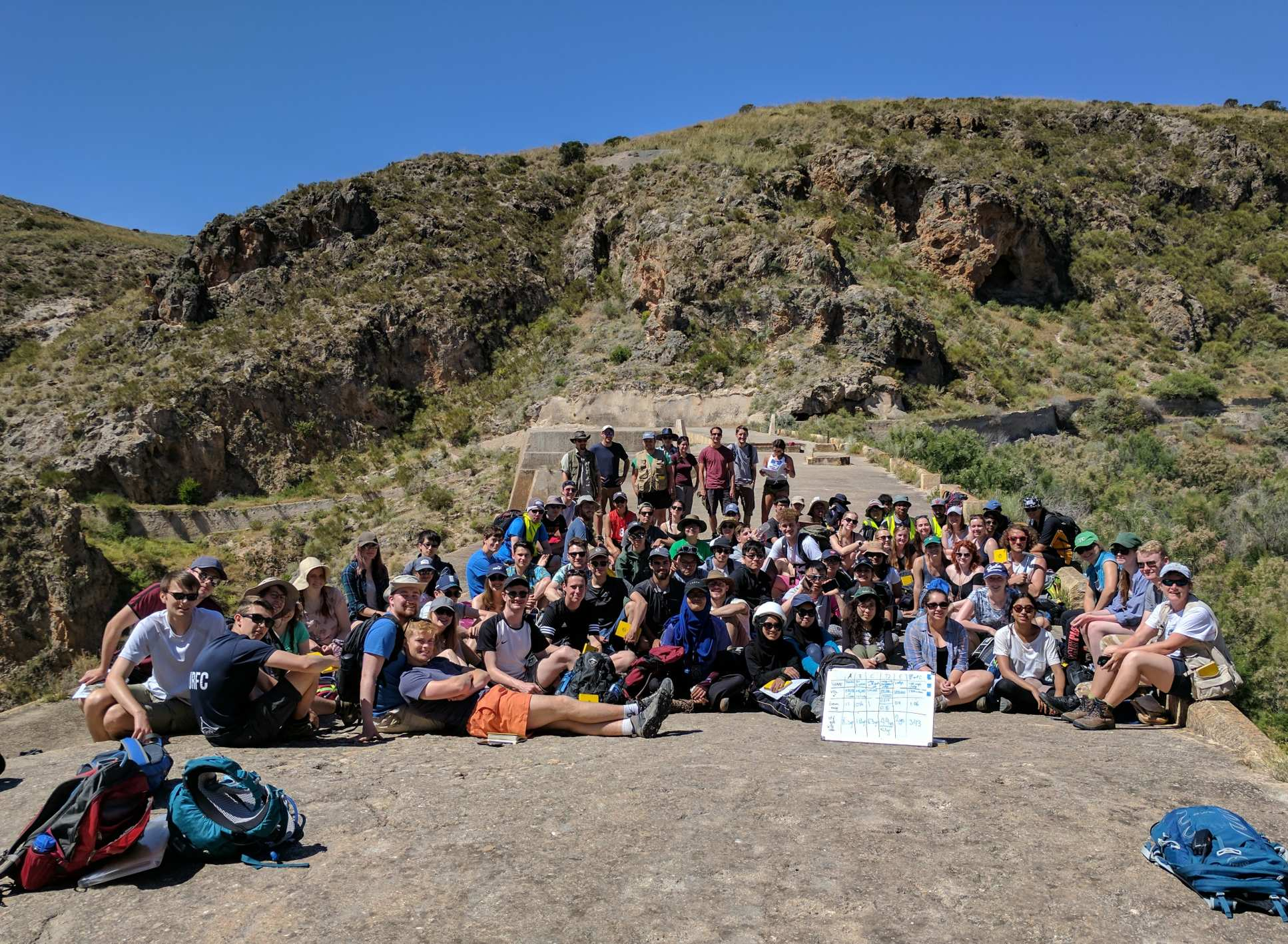 A large group of students on the 2017 Almeria field trip sit together with rocky hills in the background
