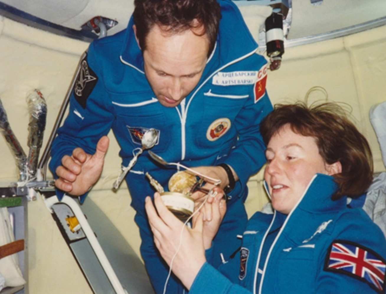 Two people eating from a can on a space station