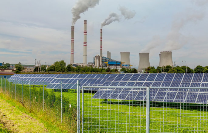 solar panels with coal and nuclear plant in background