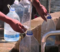 Close up of people filling up large water bottles from communal spring