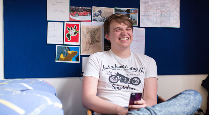 Student laughing in halls of residence room