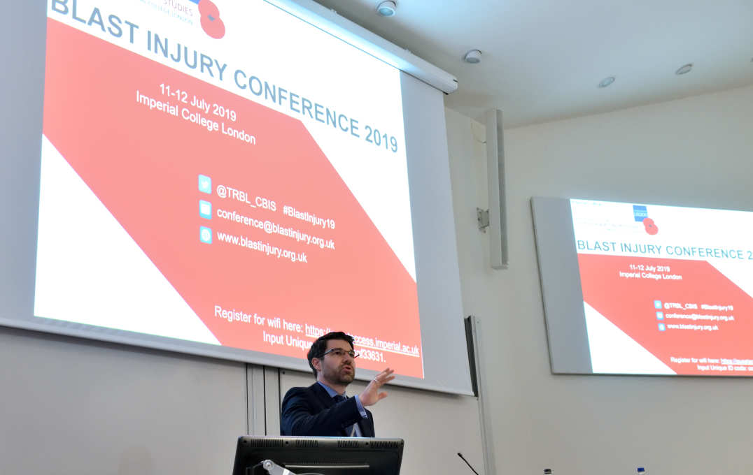 Dr Spyros Masouros, Chair of the Conference Committee, addresses the floor in front of two large screens with BLAST INJURY CONFERENCE 2019 on the slides
