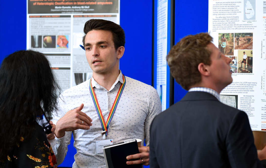 Dr Michael Berthaume explaining his work in front of a poster of his work to a female delegate